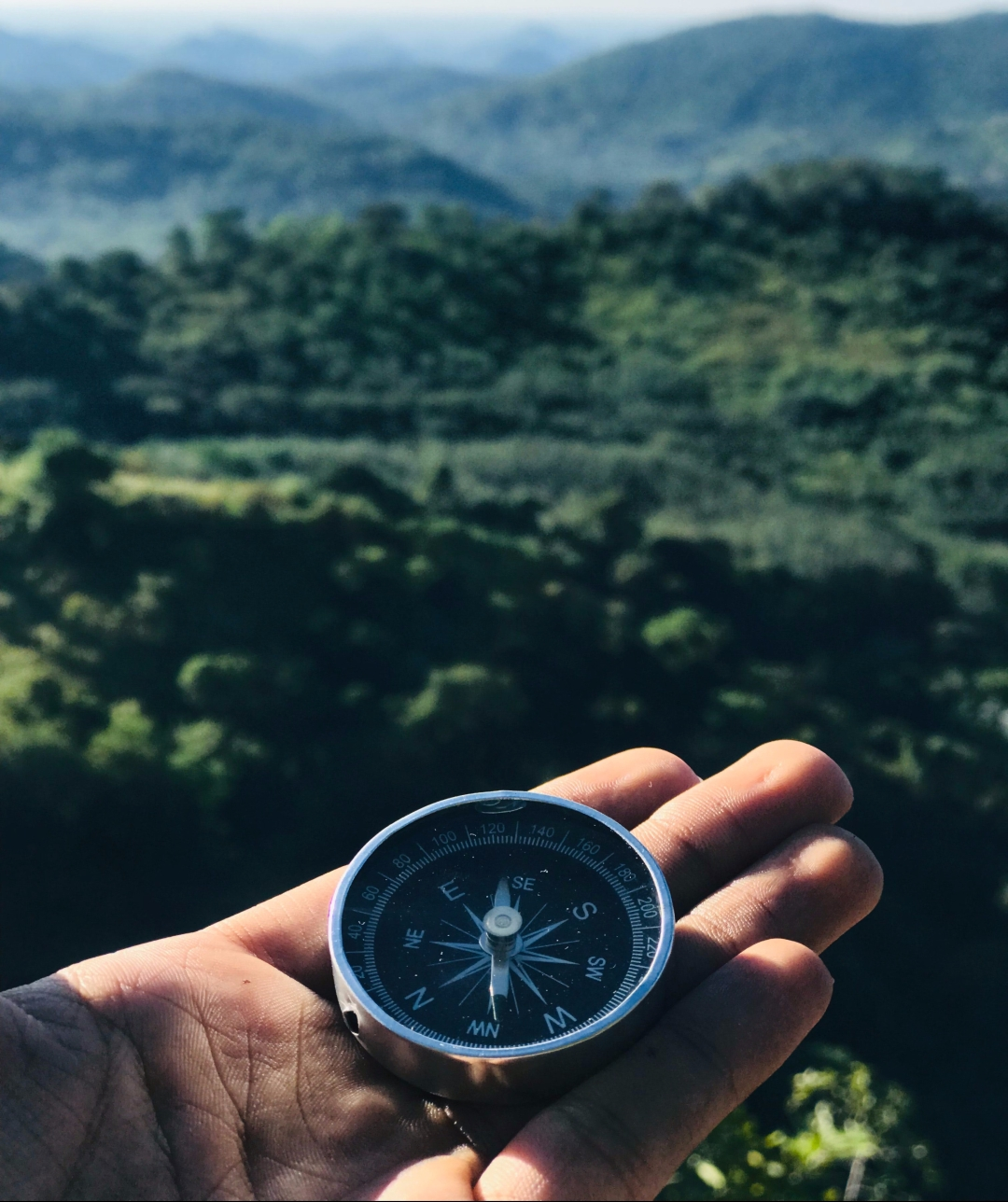 Photo of a hand holding a compass outside